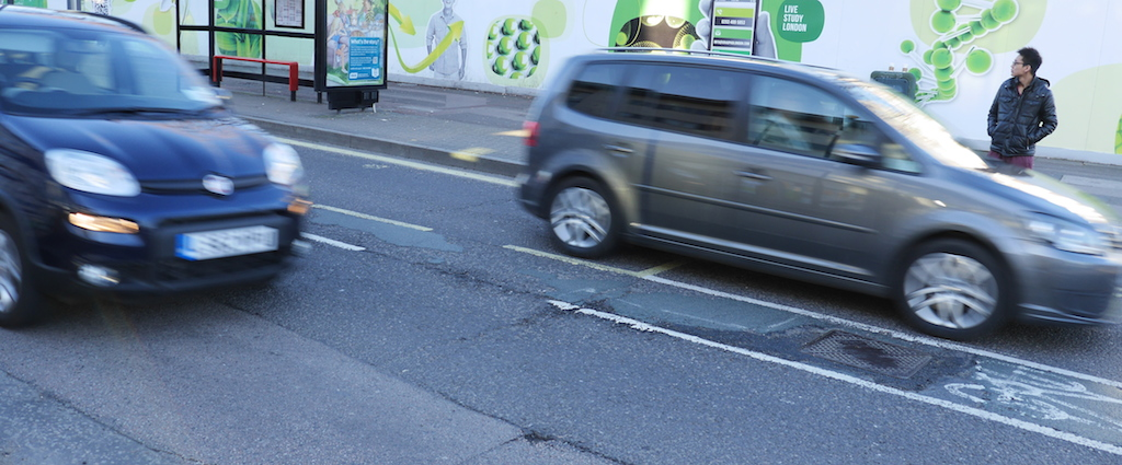 Traffic rushes past either side of the cycle lane on Wood Lane