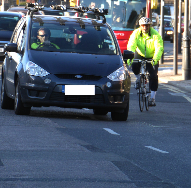 A cyclist 'negotiating' their position towards the cycle lane whilst a car driver overtakes to turn left onto the Westway.